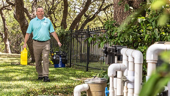 Home inspector Dave Fahrenthold walking across a lawn, carrying tools - Exactual Inspection Services.