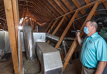 Home inspector Dave Fahrenthold inspecting an attic - Exactual Inspection Services.