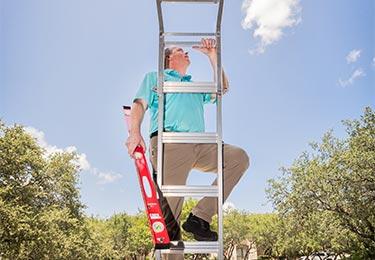 Home inspector Dave Fahrenthold climbing a latter - Exactual Inspection Services.
